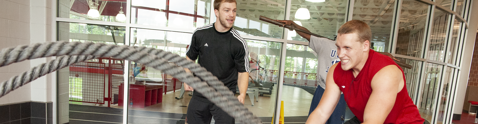 Student working out with ropes as a trainer encourages him