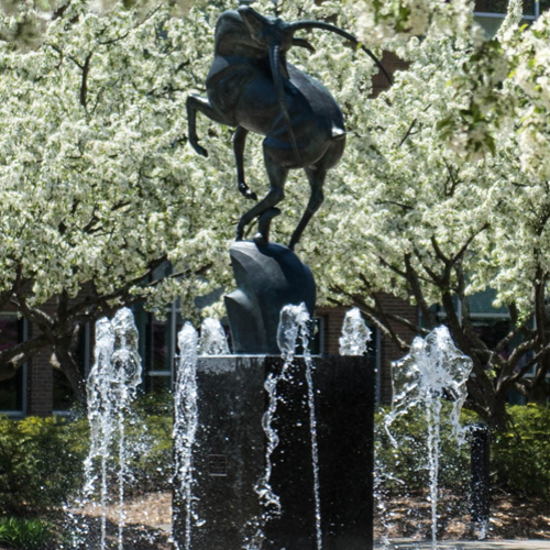 Image of the Leaping Gazelle fountain in the spring with flowering trees