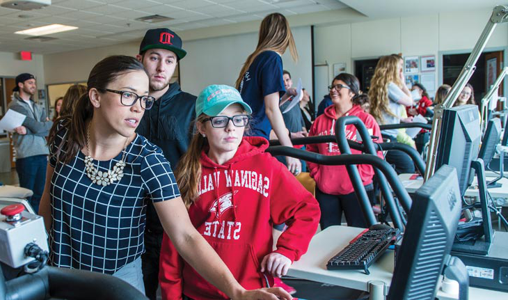 Samantha Deere with students inside exercise science lab